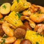 a cooked pot of shrimp boil with shrimps, sausages, corn with parsley leaves on it