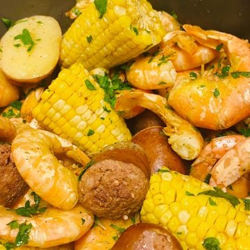 Picture of shrimps, corn, potatoes and sausages with parslley leaves
