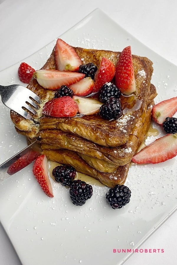A picture of cinnamon French toast served with strawberries, blackberries, confectionery sugar being cut with a fork and knife
