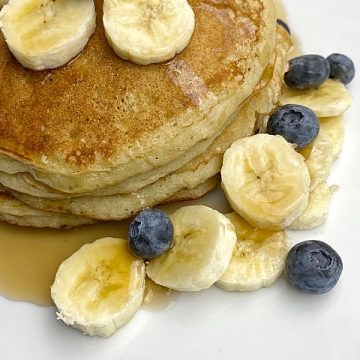 Banana pancake served with slice banana and blueberries and maple syrup