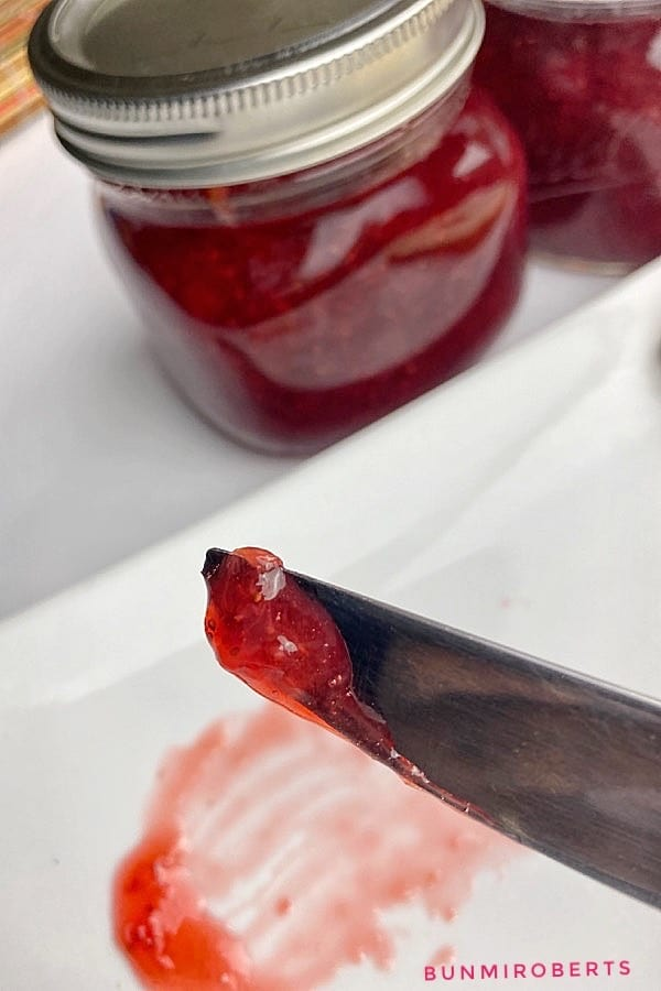 strawberry jam in a jar scooped with a knife