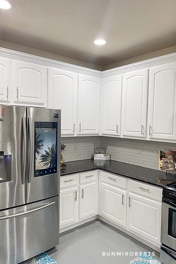 a kitchen with white cabinets, grey tile floor and white backsplash with a refrigerator