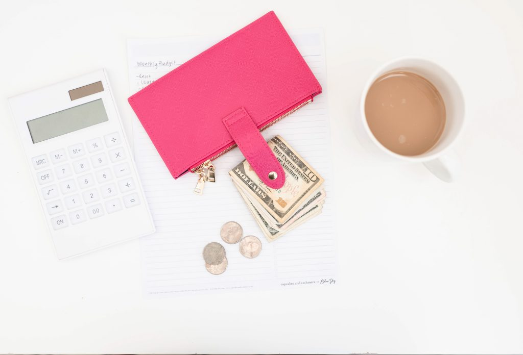 picture of a pink wallet, money , calculator and a cup of coffee
