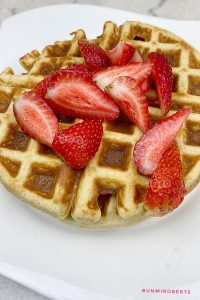 almond flour keto waffles served with cut strawberries and whipped cream