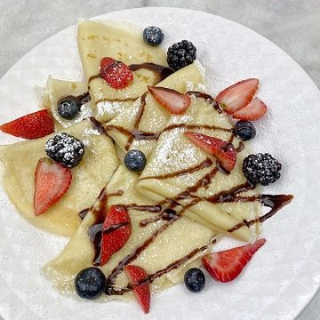 Crepes folded in quarters served with strawberries, blueberries, chocolate syrup and powdered sugar