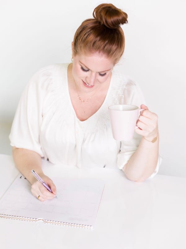 a caucasian lady drinking from a mug and writing down